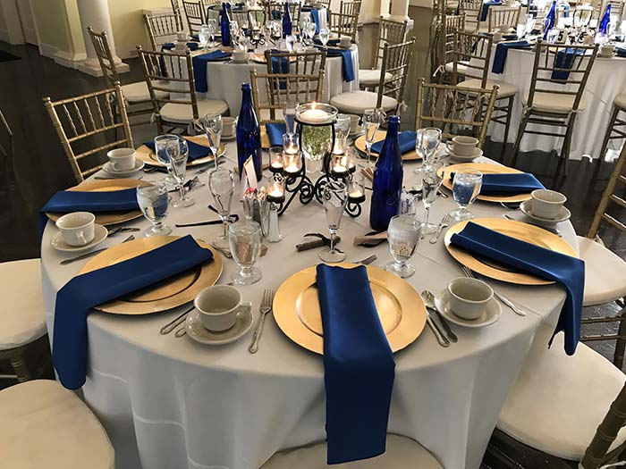 Wedding tables with dining plates and blue napkins