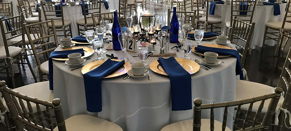 Table setting with blue napkins and gold plates